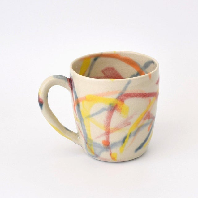 Fun, multicolor 'spray paint' mug handmade by Kim Gilmour of Fisheye Ceramics. White stoneware • Red, orange, yellow, and...