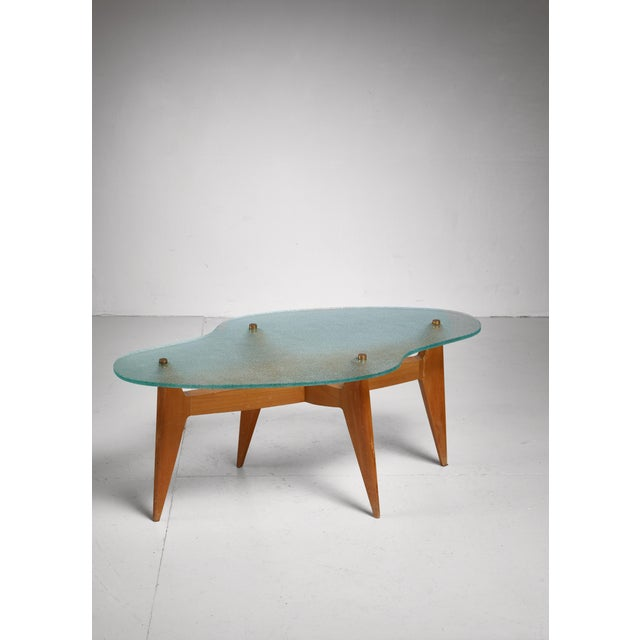A French coffee table, made of an elegant pear wood base with tapering legs and a free form thick glass top. We have a...