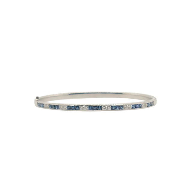 A fine 18K white gold bangle bracelet with 21 channel set princess cut natural sapphires and 12 round cut diamonds. There...
