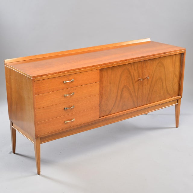 Circa 1950s English blond walnut sideboard features four drawers and a cabinet section with an internal shelf. Beautiful...