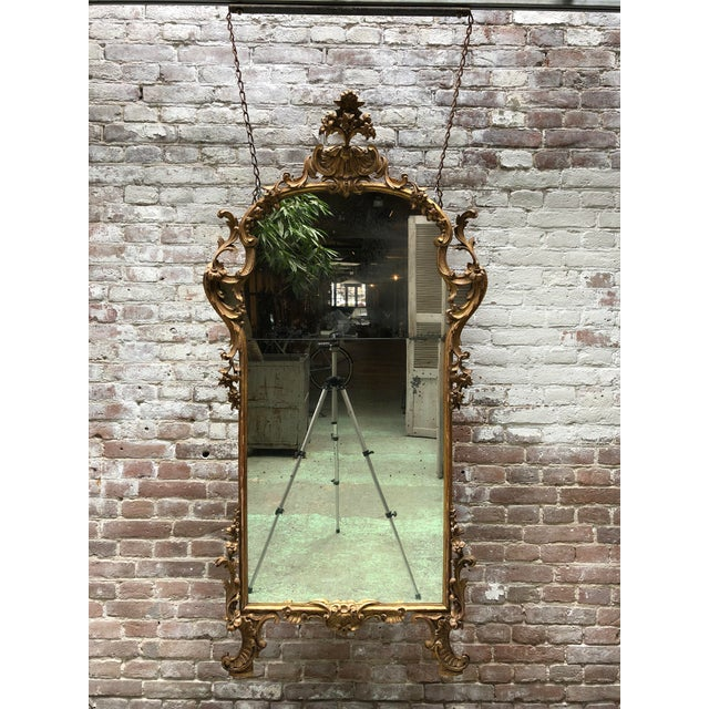 A Fine Italian Rococo Giltwood Mirror, mid-18th Century,Tuscany Mirror surmounted by an elaborate pierces arched top crest...