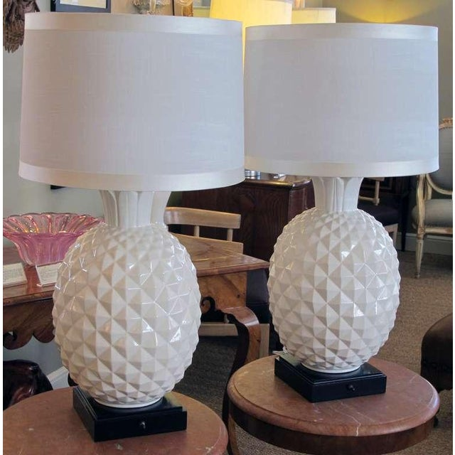 A robust and large-scaled pair of Italian 1960's white ceramic pineapple-form lamps; each portly lamp depicting a plump...