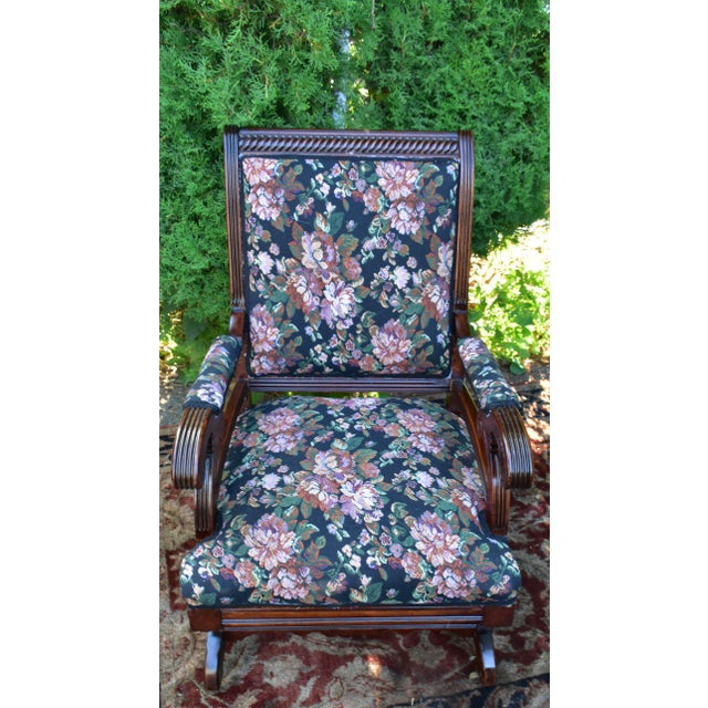 This Rocking chair features a high upholstered Back / Seat and upholstered arms with rolled hand rest. Carved details on...