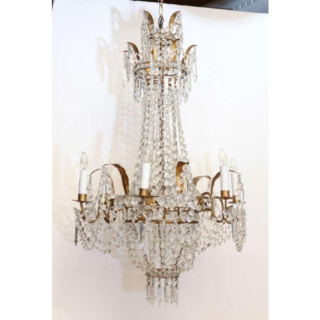 Chandelier, in beaded basket form, of gilded iron, surmounted by double crown with gilded leaves draped with beads and...