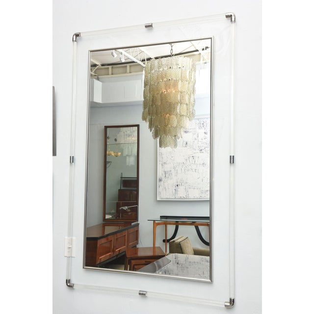 the polished chrome and lucite frame with a lucite backing to have the polished chrome banding and mirror to appear floating