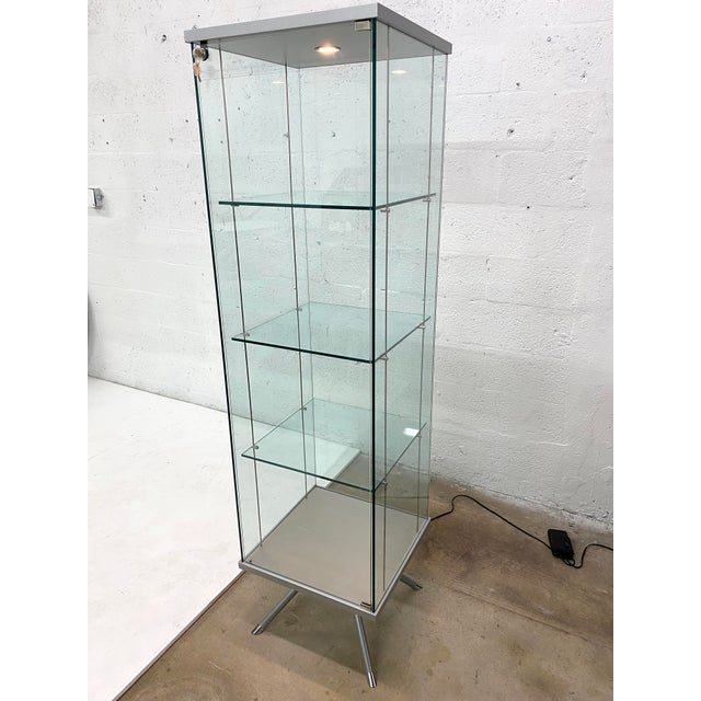 Glass and steel curio display cabinet with suspended glass shelves for art and objects. The lamp is dimmable.