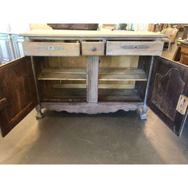 This French provincial Louis XV style buffet has 3 drawers over 2 cabinet doors. It is circa late 18th century, and is in...