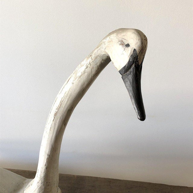 Folk art carved wooden swan in old white and black paint.
