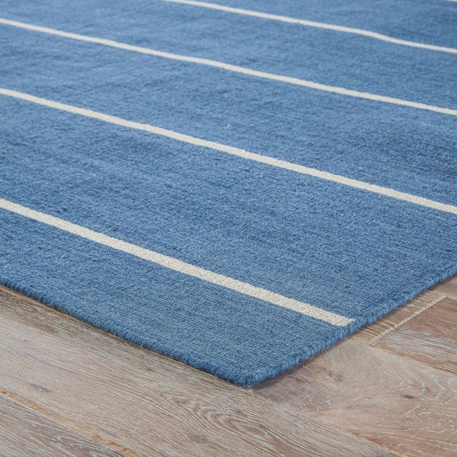 Classic with a bold stripe, this nautical dark blue and creamy white flatweave area rug lends traditional charm to any...