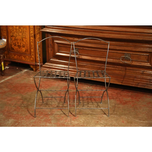 Place this pair of antique side chairs around a bistro table on a covered patio. Forged in France circa 1880, the iron...
