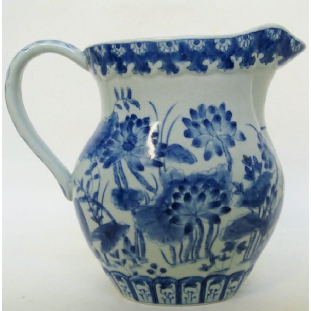 Chinese porcelain pitcher with hand-painted floral designs in blue on very pale celadon glaze. Maker's mark on underside.