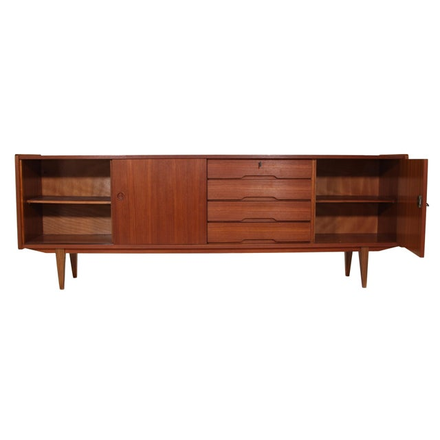 Outstanding German teak credenza. Featuring 2 sliding doors on the left and 4 drawers in the middle of the credenza. It...