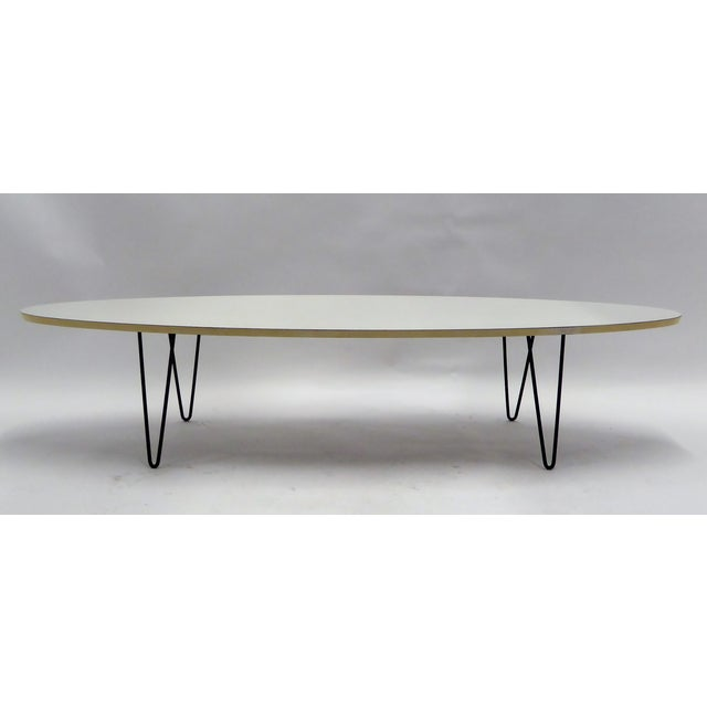 Mid-century classic look with this period Surfboard coffee cocktail table on hairpin Legs. With an elliptical white...