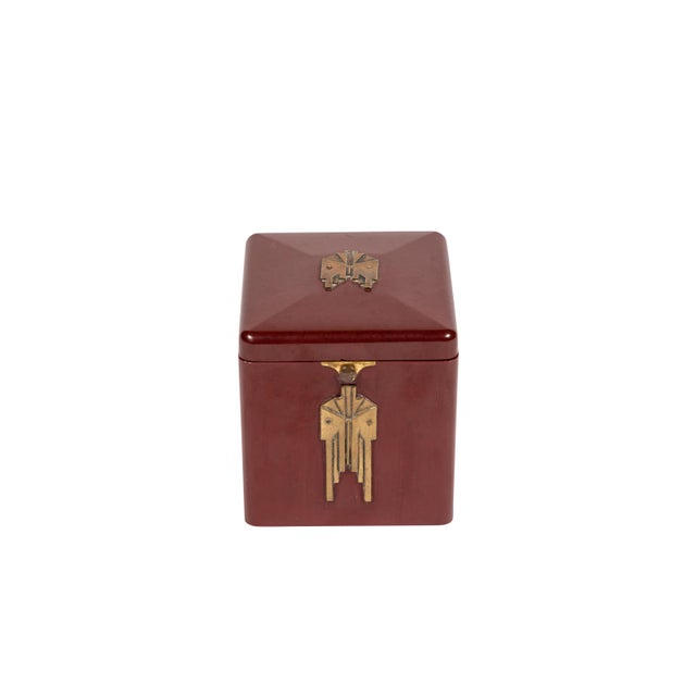 Art Deco burgundy square Bakelite box with period brass detailing. Interior has room for twenty-four cigarettes and has a...