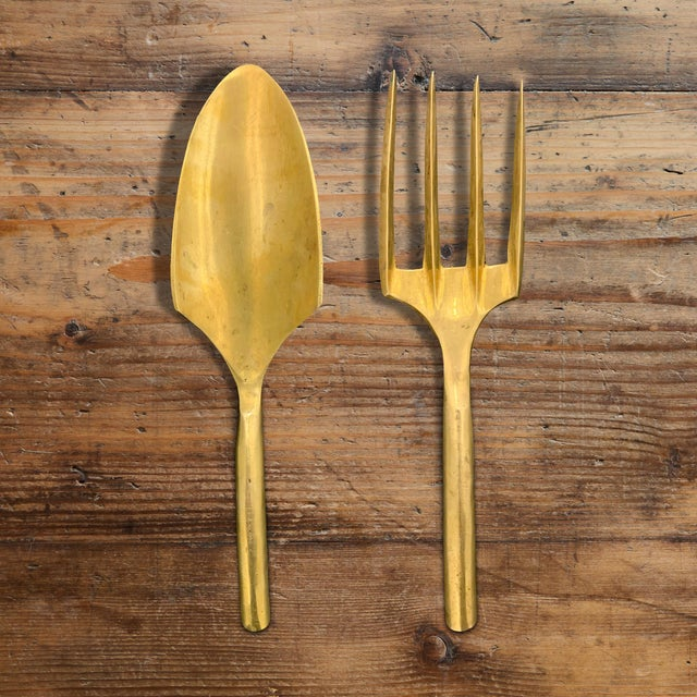 Pair of brass garden tools including a shovel and a hand rake and ergonomic handles.