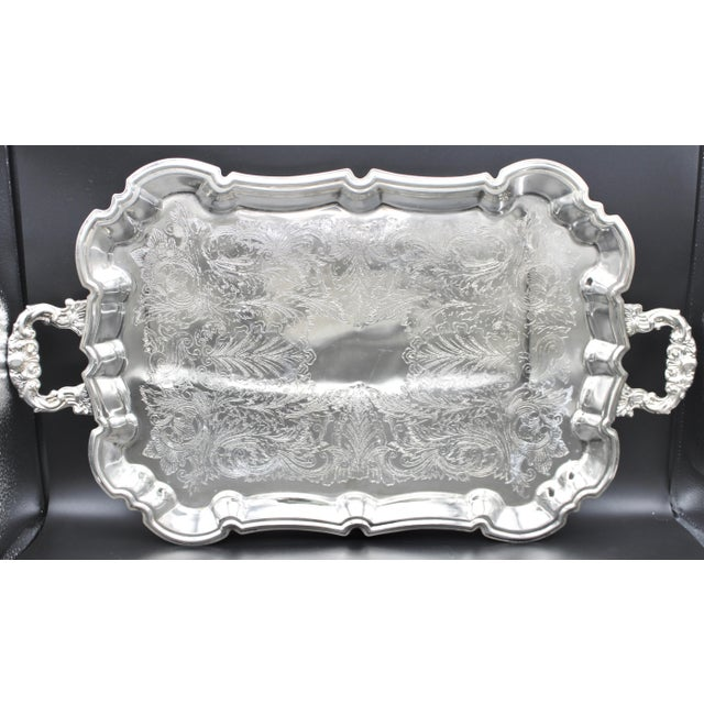 A lovely, silver plated tray from France, crafted circa 1950s. This elegant serving tray sits on four detailed feet and...