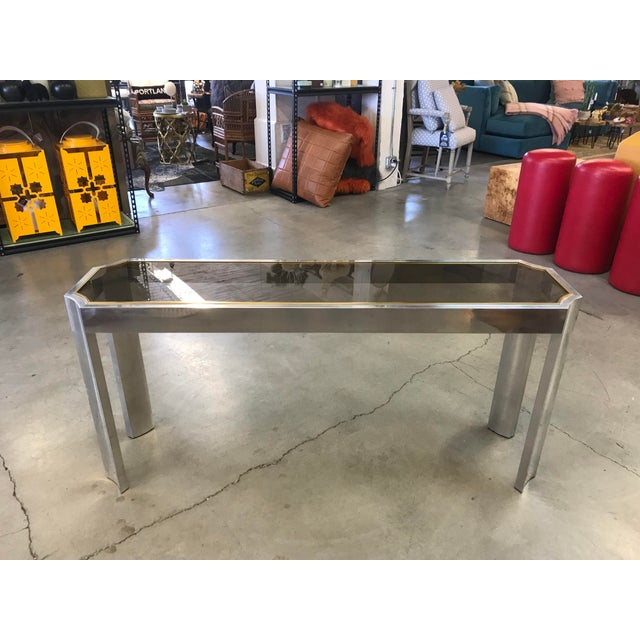 Beautiful 1970s console table, chrome metal frame with brass accent and smoked glass top.