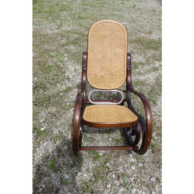1970s style Thornet Style Rattan Rocking chair. Some light scratches. Back and seat are in excellent condition.