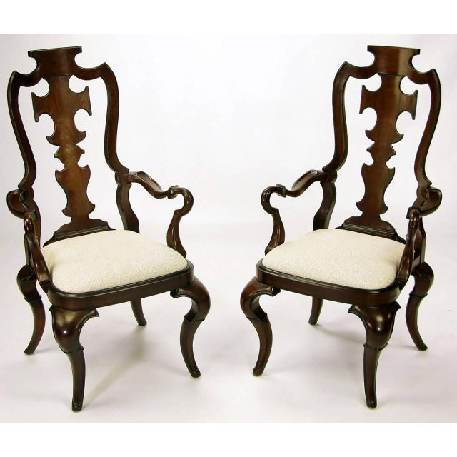 Dark walnut wood chairs with carved back splats in a unique design, as well as unusual arms. Cabriole legs on all four...