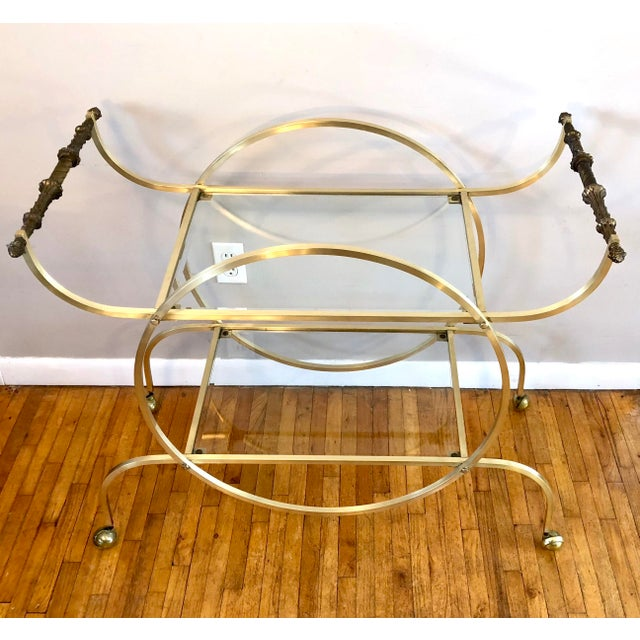 An elegant and unusual vintage Mid Century Modern / Hollywood Regency Bar cart in solid brass tubing with beveled glass...