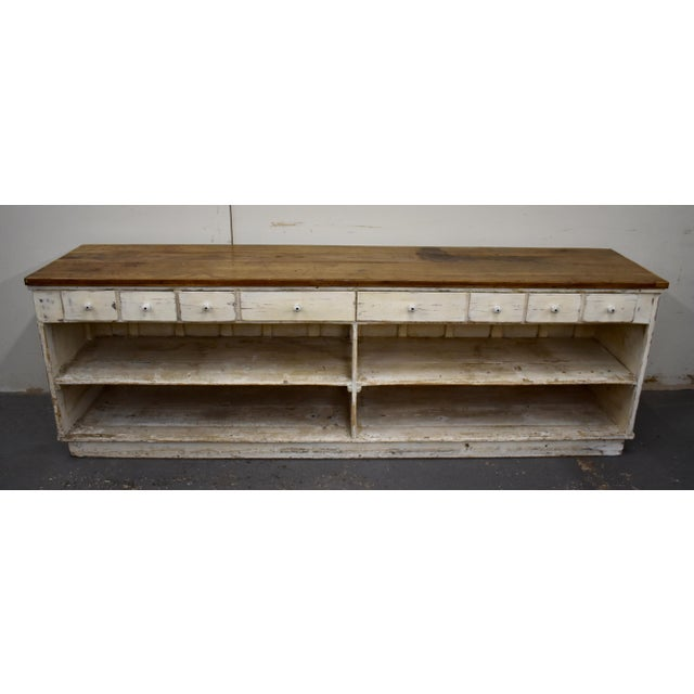 This is a huge vintage store counter with a pine base, one side of which is entirely plain except for four applied...