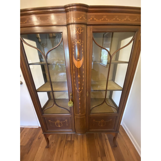 Circa 1910 Adams Mahogany China Cabinet with the original satin lining. Two astragal glazed doors divided by a bellflower...