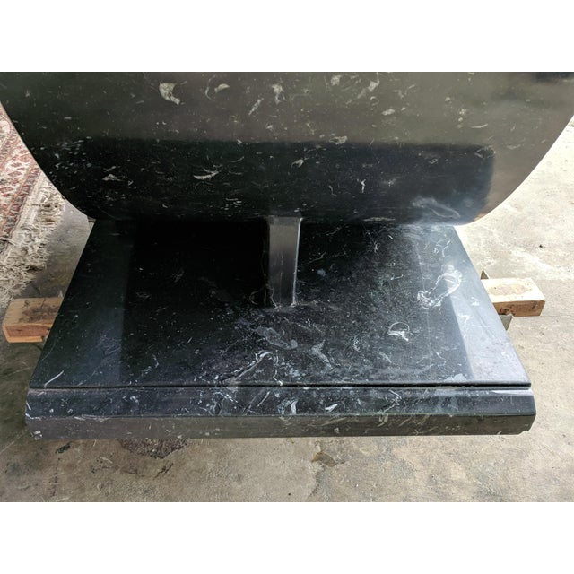 A monumental granite table. Art Deco style with with fluted columns and scroll-work. Grayish onyx color with flakes of...