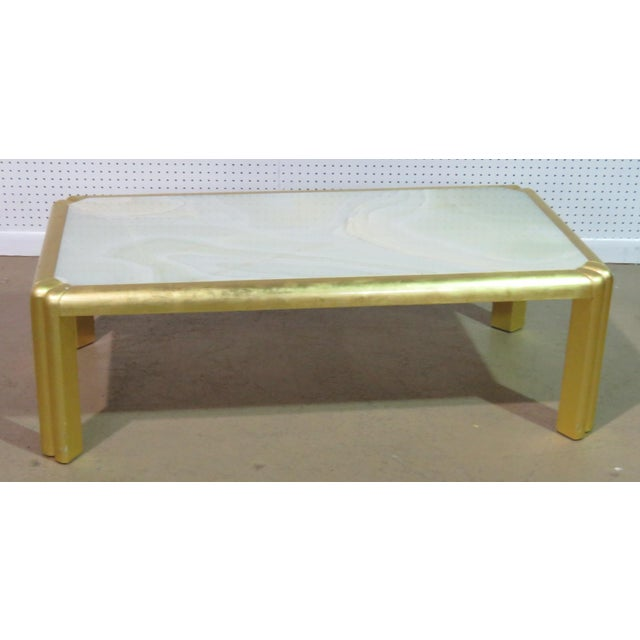Hollywood Regency style coffee table with a gilt frame and a stone top.