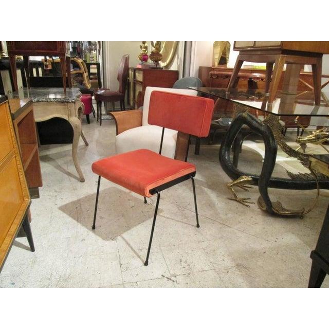 A set of four Italian, velvet-upholstered iron chairs.