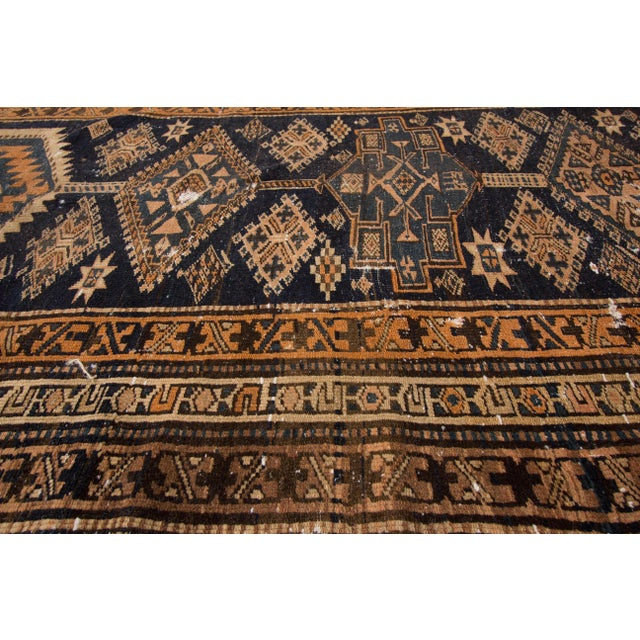 An antique hand-knotted Heriz rug with a geometric design on a blue field with brown borders. This rug has magnificent...