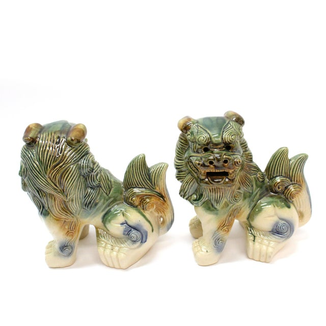 Beautiful pair of mid-century glazed pottery Foo dogs. Each is one hand-painted glazed pottery in earth tone colors of...