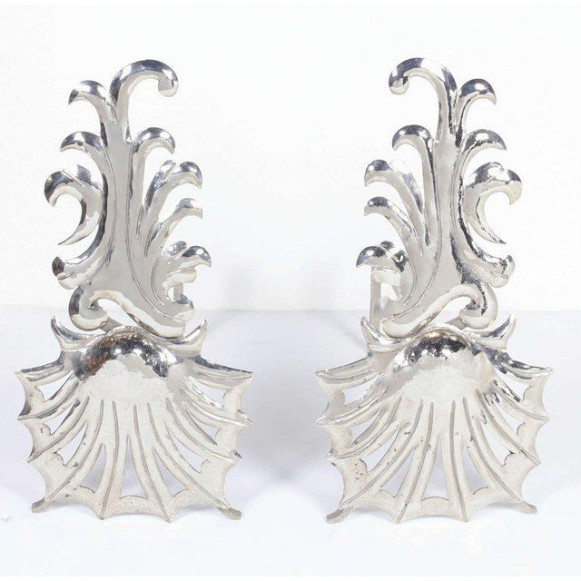 Pair of elegant fireplace andirons with stylized shell design and wave patterns. Polished nickeled finish over steel and...