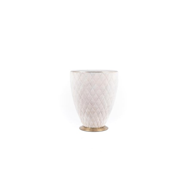 The Coco Stool in cream shagreen is an elegant piece with its beautiful quilted detailing and bronze-patina brass border....