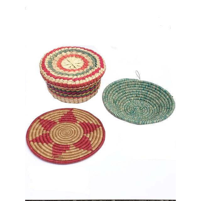 Set of lovely baskets- all practical, bright & can be hung on the wall for decoration. A trivet measuring 9.5 x .5 A bowl...