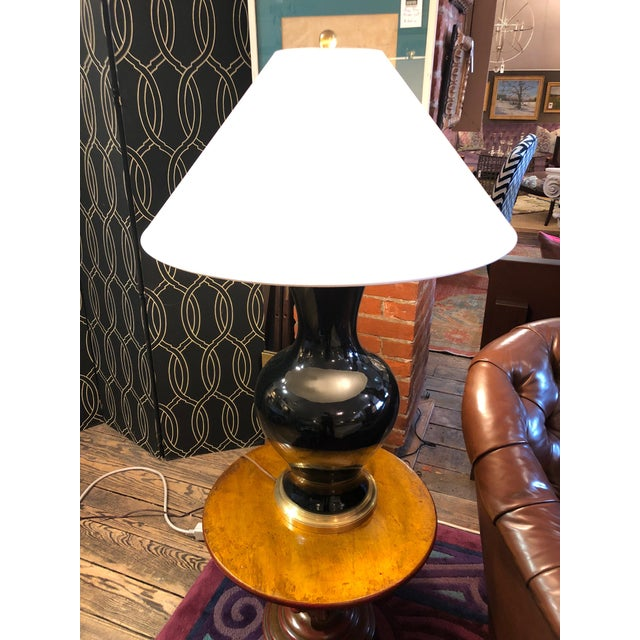 A statement lamp for its impressive size having a shiny black vase shaped base with brass accents and a huge custom paper...