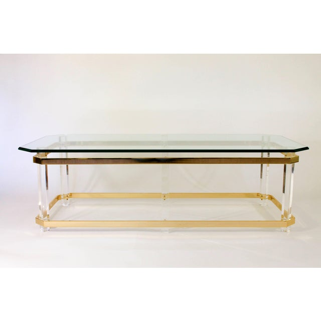 Rectangular Hollywood Regency brass and Lucite cocktail table in the manner of Charles Hollis Jones. No maker's mark....