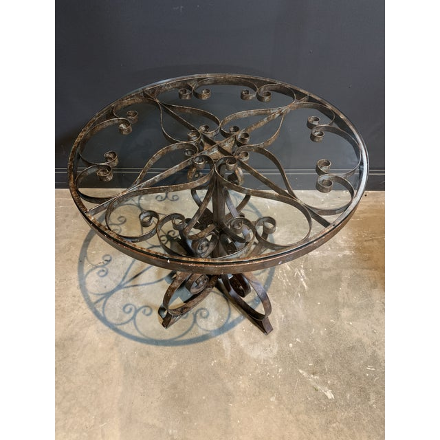 Rustic iron frame and glass top bistro table.
