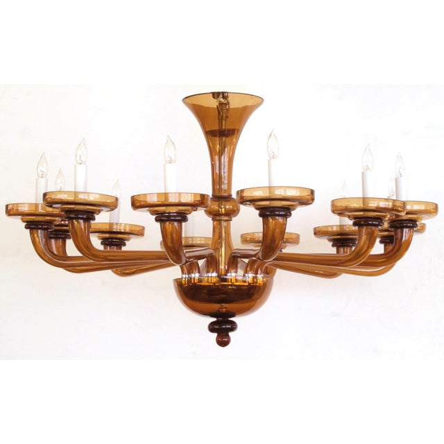 A large and richly-colored Murano twelve-light amber glass chandelier; centering a baluster-form support emanating 12...