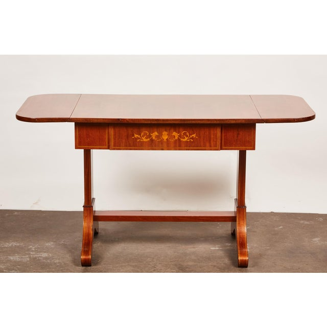 A 19th century Empire mahogany salon table of rectilinear simplicity, featuring a pair of drop leaves and delicate inlay...