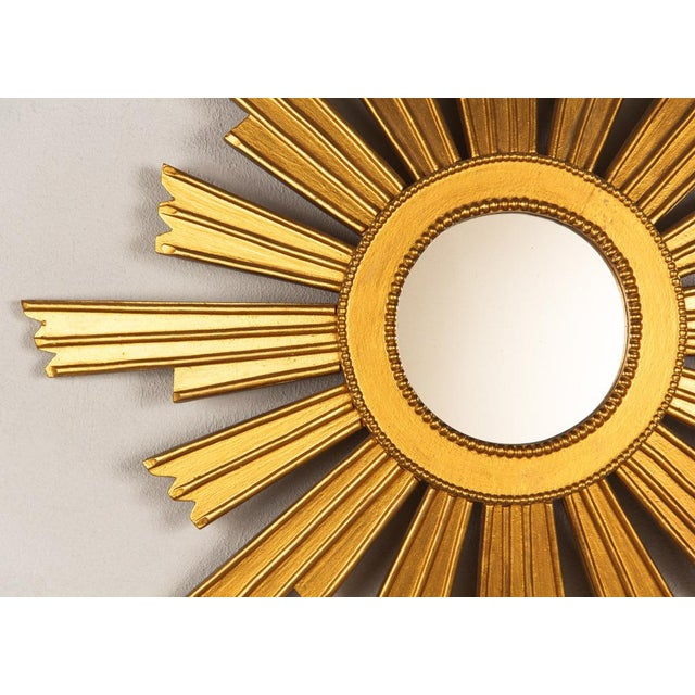 "A mid-century giltwood sunburst mirror, French circa 1950. At the center is a 4.75"" mirror framed by a raised gilt rim..."