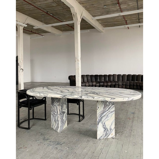 Oval marble slab dining table with triangular pedestal legs. The brilliant cut of marble is veined with meandering lines...