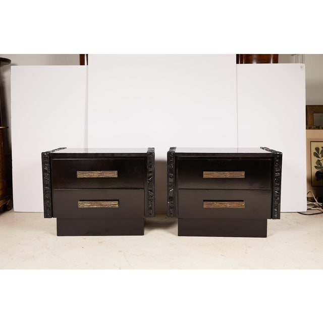 Vintage pair of midcentury nightstands or end tables with heavy brutalist carvings on each side flanking a case holding...