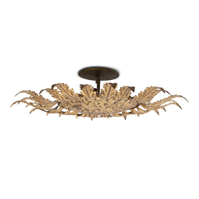 Gilt tole flush mount light for your ceiling or wall. Sunburst design of gilt tole leaves radiating from a gilded hammered...