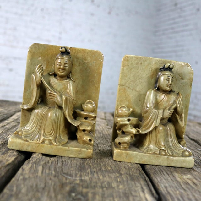 Handsome and intricately carved Chinese soapstone bookends depicting Asian seated figures and teapot detail. They are in...