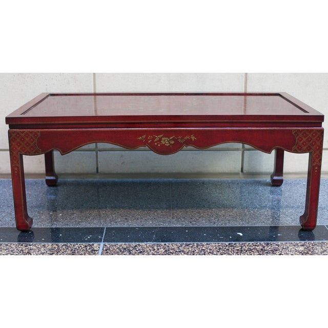 Chinoiserie coffee or cocktail table in a dark red or oxblood coloration. The hand painted gilt decoration is of flowers...