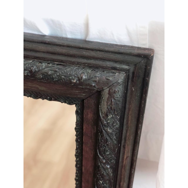 Stately antique wood framed mirror with newer glass. Wood frame boasts a lovely relief design and is fairly light-weight....