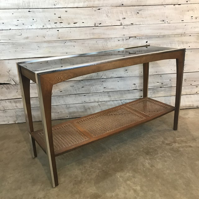 Beautiful Walnut and Chrome Console/ Sofa Table. This table exhibits and woven Rattan shelf surrounded by walnut on the...