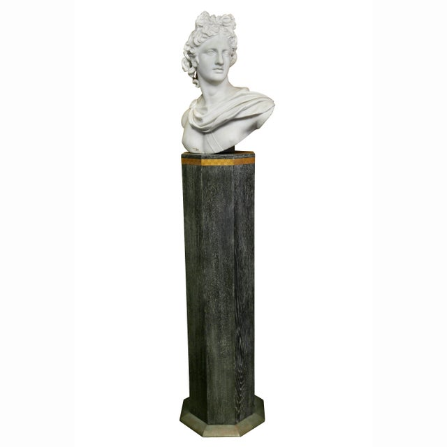 With his head facing right. Hair knotted. Wearing a tunic with a medallion. The octagonal cerused oak pedestal with...