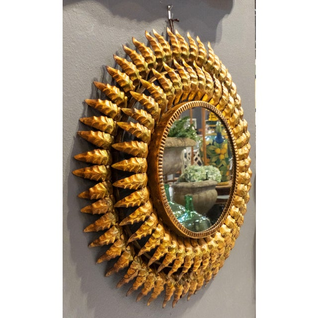 A lovely French sunburst (or starburst) mirror of gilt metal, 20 inches diameter, with round mirrored glass center in...