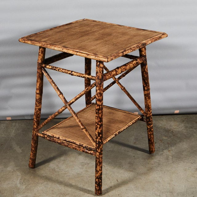 This English victorian tiger bamboo side table is of a great size with criss-cross supports and a lower shelf. All of our...